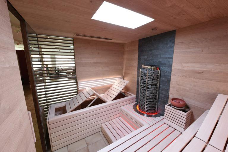 Sauna mit Steinrückwand und Glas